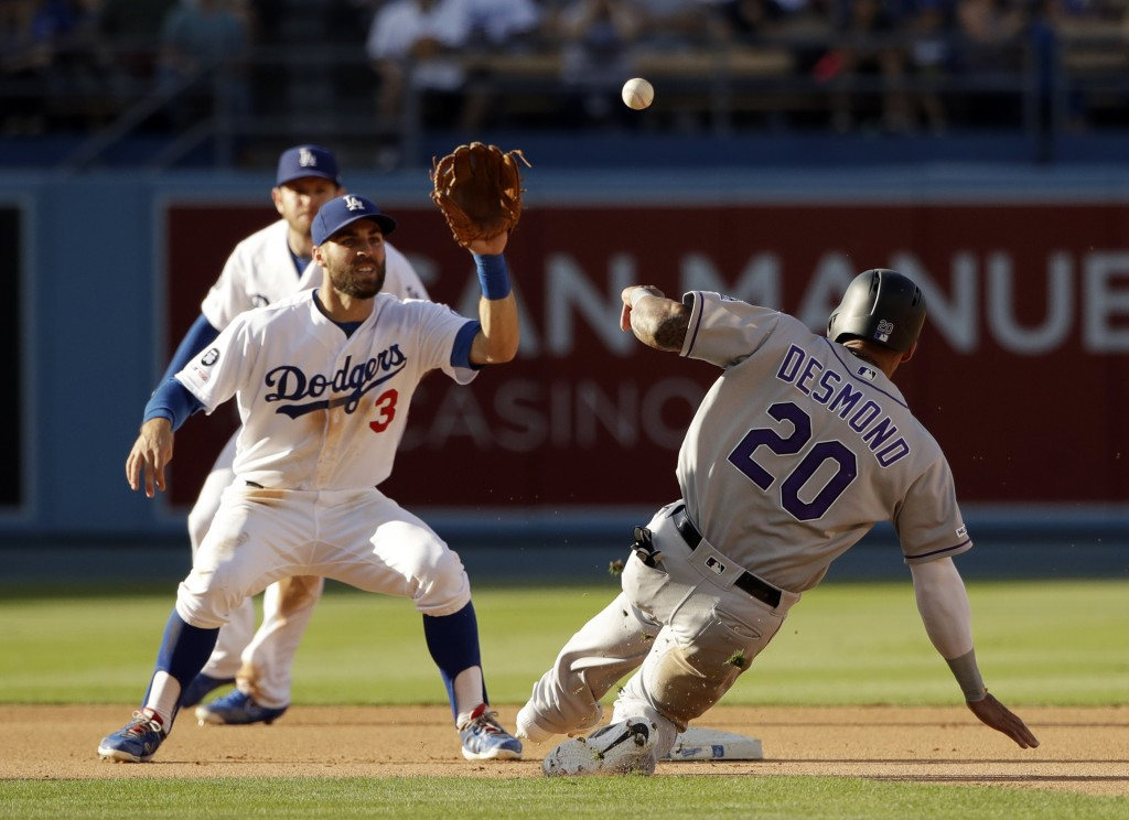 Los Angeles Dodgers shortstop Chris Taylor, left, gets the throw from first base to tag out Colorado Rockies' Ian Desmond (20) on a steal attempt duri...