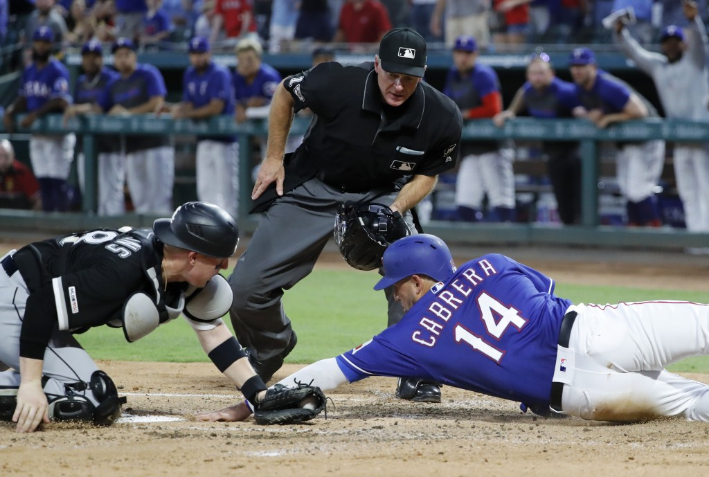 Chicago White Sox catcher Zack Collins, left, reaches to tag out Texas Rangers' Asdrubal Cabrera (14) as umpire Ed Hickox looks on in the first inning...