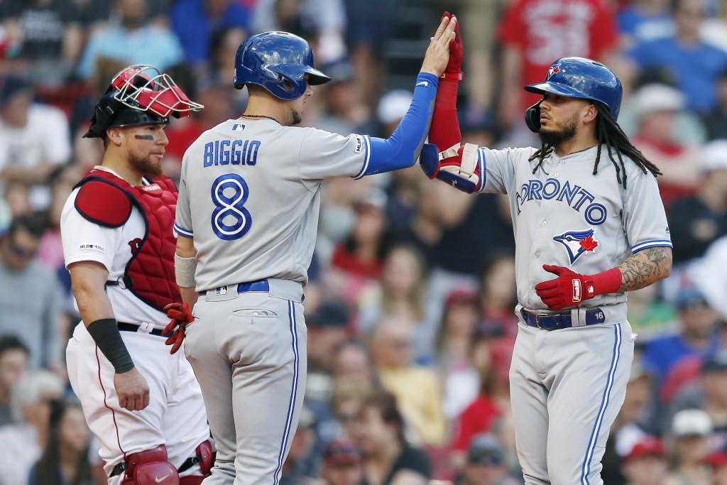 Toronto Blue Jays' Freddy Galvis, right, celebrates his two-run home run that drove in Cavan Biggio (8) as Boston Red Sox's Christian Vazquez stands n...