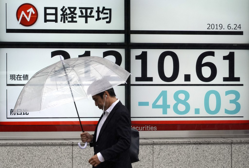 A man walks past an electronic stock board showing Japan's Nikkei 225 index at a securities firm in Tokyo Monday, June 24, 2019. Shares were wavering ...