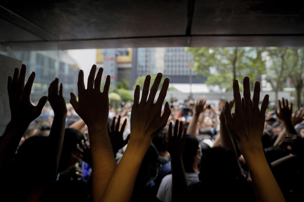 Protesters gesture inside the Hong Kong Revenue Tower as they block the building lobby to prevent people from entering in Hong Kong, Monday, June 24, ...