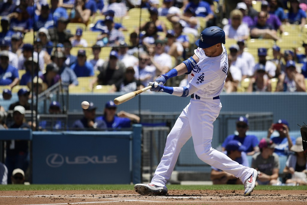 Los Angeles Dodgers' Cody Bellinger hits a foul ball that struck a fan in the stands during the first inning of a baseball game against the Colorado R...