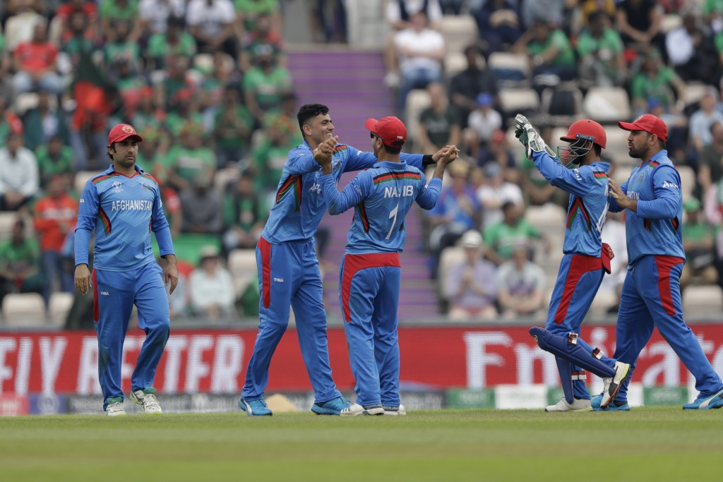 Afghanistan's Mujeeb Ur Rahman, second left, celebrates taking the wicket of Bangladesh's Shakib Al Hasan during the Cricket World Cup match between B...