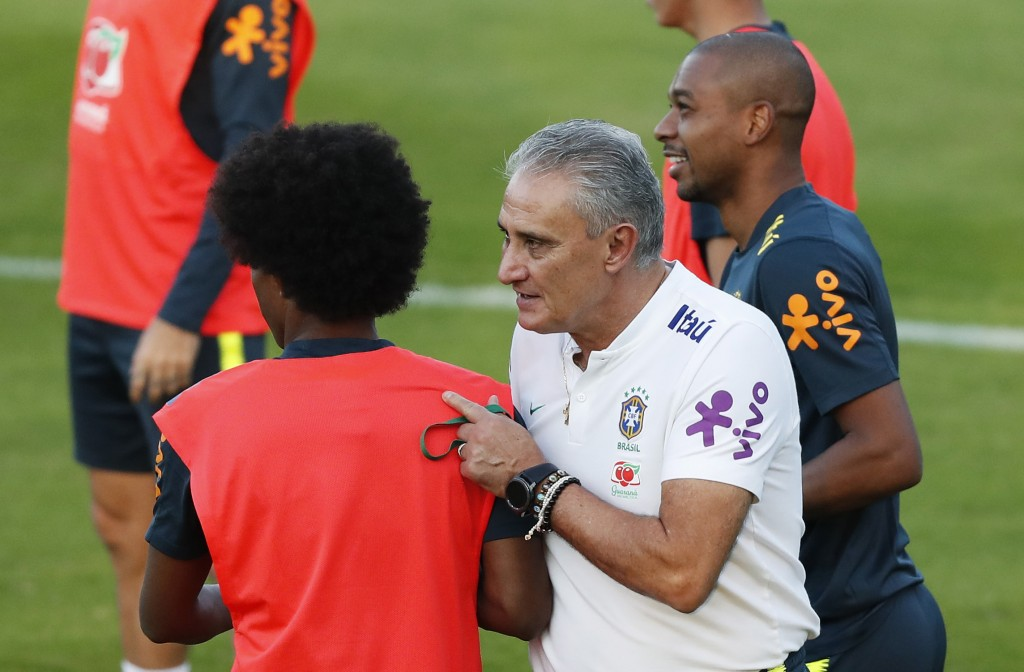 Brazil's coach Tite speaks with his player Willian, left, as  Fernandinho walks behind, during a training session by the national soccer team in Sao P...