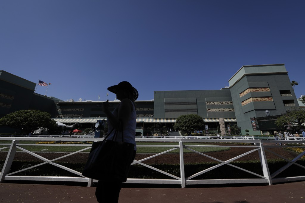 A horse racing fan waits for the fifth race near the paddock during the last day of the winter/spring meet at the Santa Anita horse racing track Sunda...