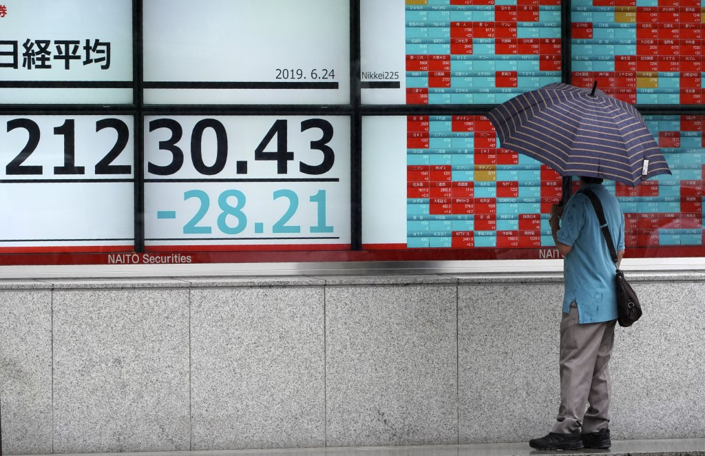 A man looks at an electronic stock board showing Japan's Nikkei 225 index at a securities firm in Tokyo Monday, June 24, 2019. Shares were wavering in...