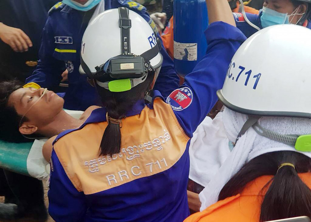 In this photo provided by the Preah Sihanouk Provincial Authority, rescuers carry a survivor from the site of a collapsed building Monday, June 24, 20...