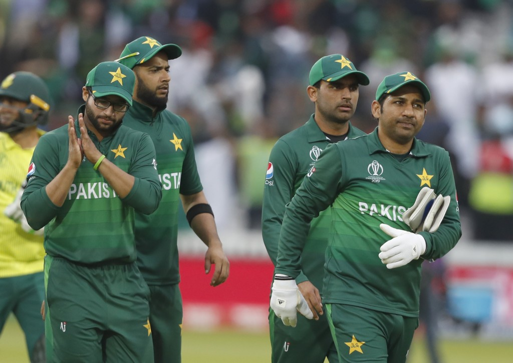 Pakistan's captain Sarfaraz Ahmed right leads the team from the field as they celebrate after they defeated South Africa by 49 runs in their Cricket W...