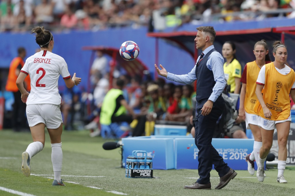 England head coach Philip Neville passes the ball to England's Lucy Bronze, left, during the Women's World Cup round of 16 soccer match between Englan...