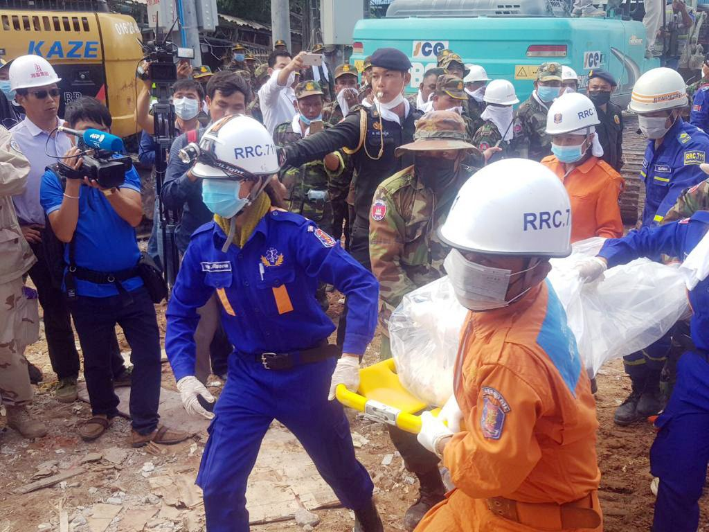 In this photo provided by Preah Sihanouk Provincial Authority, rescuers carry the body of a victim at the site of a building collapse, Monday, June 24...