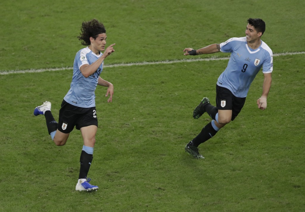 Uruguay's Edinson Cavani, left, celebrates with teammate Luis Suarez after scoring his side's first goal against Chile during a Copa America Group C s...