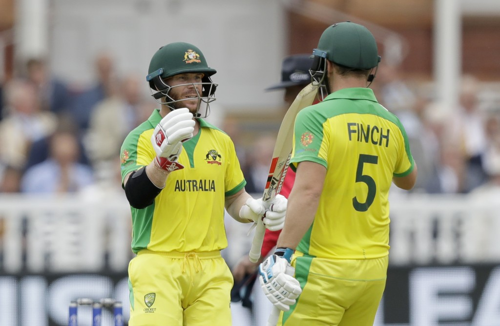 Australia's David Warner, left, celebrates reaching 50 runs with Australia's captain Aaron Finch during the Cricket World Cup match between England an...