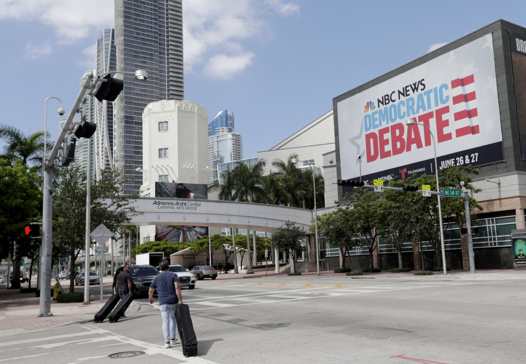 In this June 24, 2019, photo, a billboard advertises the Democratic Presidential Debates across from the Knight Concert Hall at the Adrienne Arsht Cen...