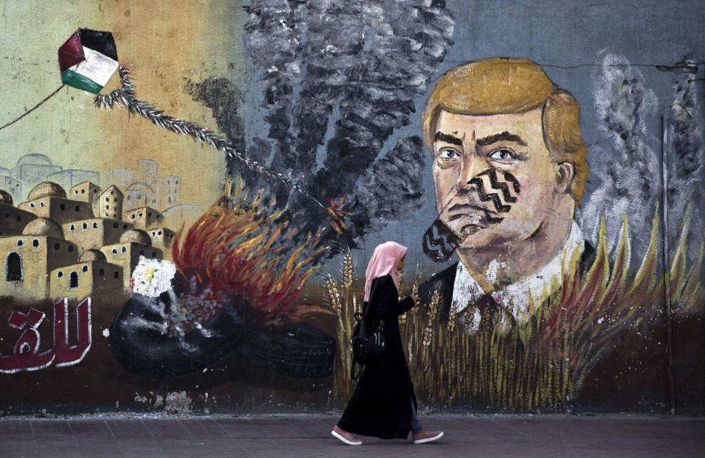 A wall with graffiti depicts U.S. President Donald Trump with a footprint on his face in Gaza City, Tuesday, June 25, 2019. Palestinians in the Gaza S...