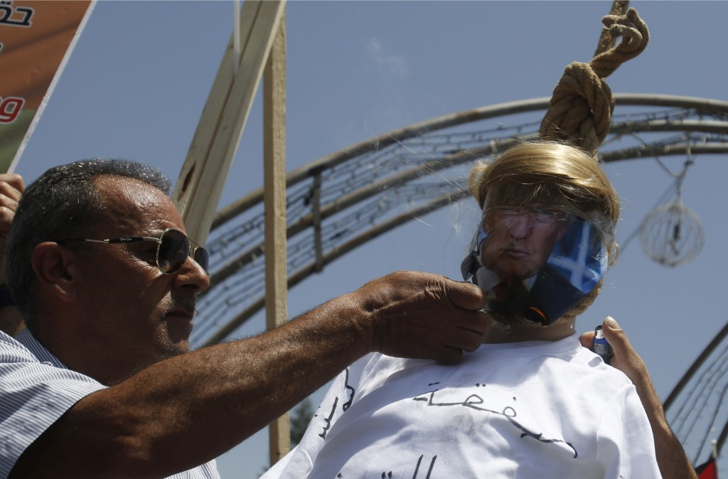 A Palestinian burns an effigy of the US President Donald Trump aduring a protest against the American-led Mideast peace conference in Bahrain, in the ...