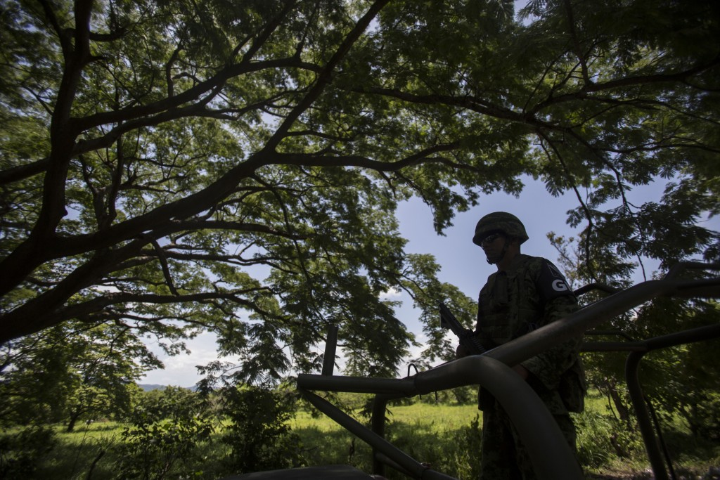 A member of the National Guard takes part in an operation in search of undocumented migrants in a forest near Arriaga, Mexico, Monday, June 24, 2019. ...