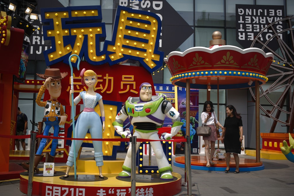 "A woman browses her photo after taking with her friend near the American latest animated film ""Toy Story 4"" promotion decoration on display at the cap..."
