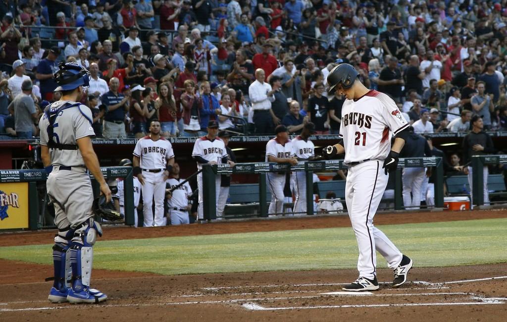Arizona Diamondbacks' Zack Greinke (21) arrives at home plate after hitting a home run as Los Angeles Dodgers catcher Austin Barnes, left, pauses near...