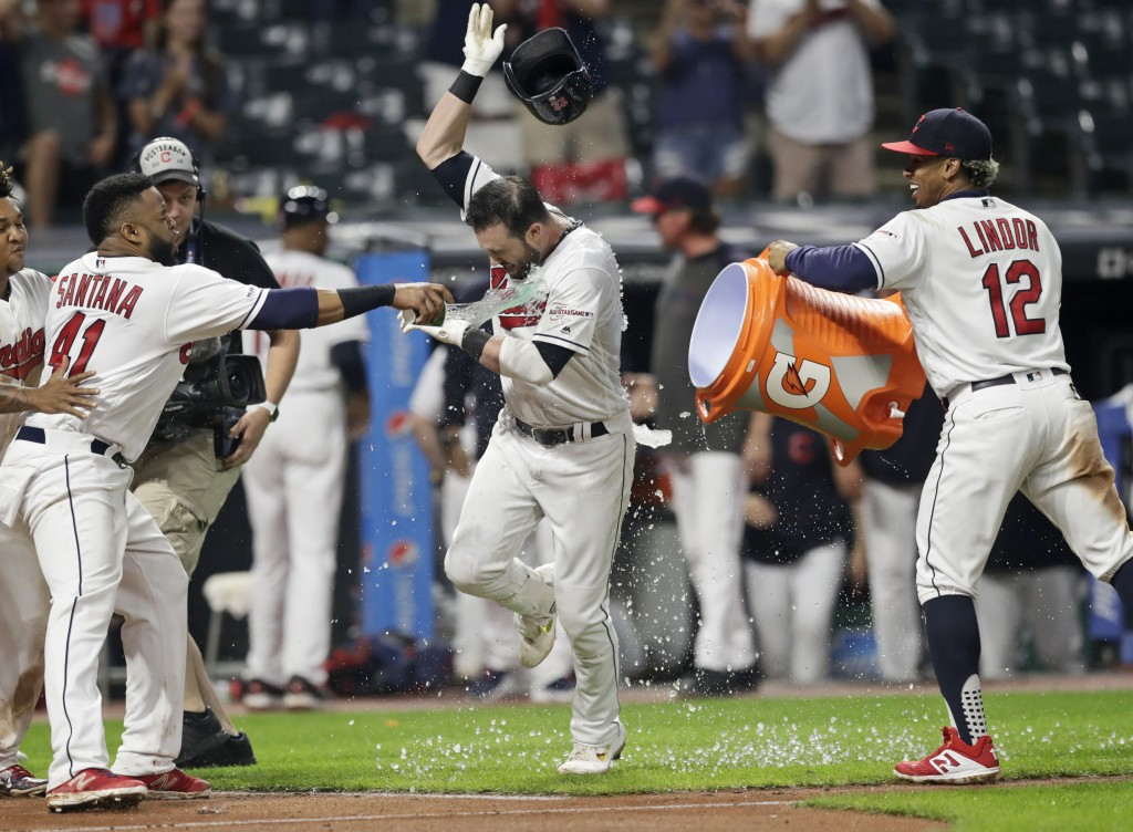 Cleveland Indians' Jason Kipnis, center, is doused with water from Cleveland Indians' Carlos Santana, left, and Francisco Lindor, right, after hitting...