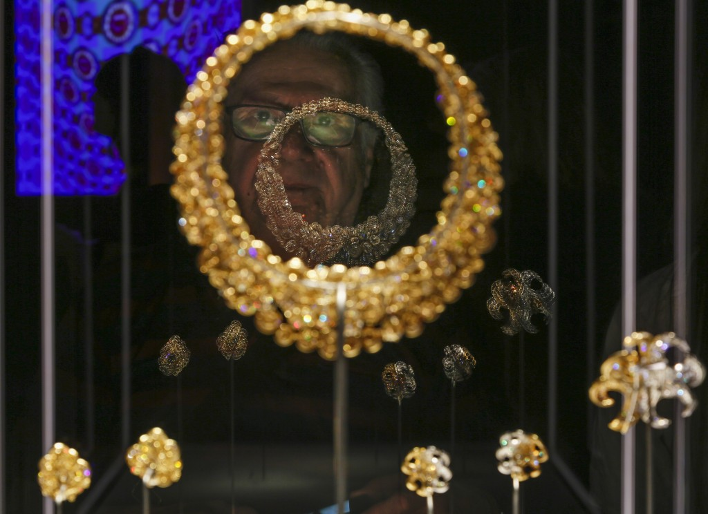 """A man looks at a Bulgari necklace and earrings in gold with diamonds from 1969 during a preview of the exhibition """"Bulgari. The story, the dream"""" at S..."""