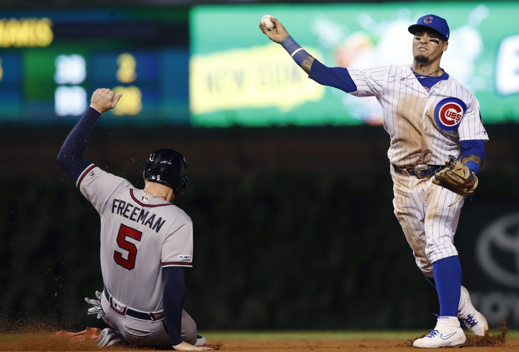 Atlanta Braves' Freddie Freeman, left, is out sliding into second base as Chicago Cubs' Javier Baez, right, throws to first base during the eighth inn...
