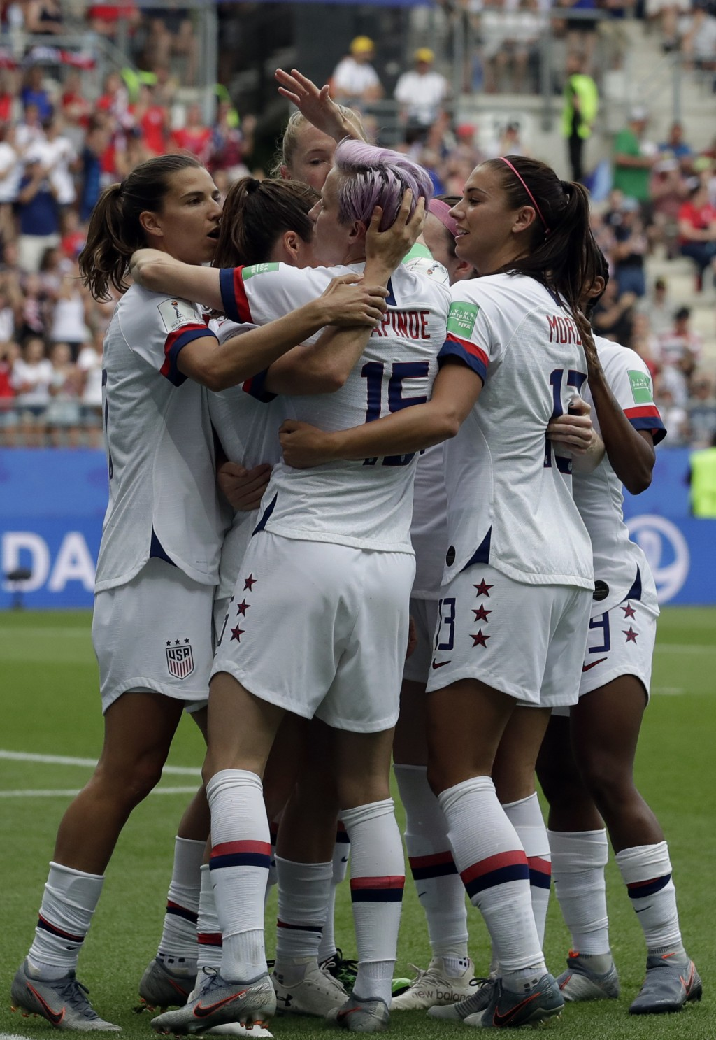 United States' Megan Rapinoe, front, celebrates with teammates after scoring the opening goal from a penalty spot during the Women's World Cup round o...