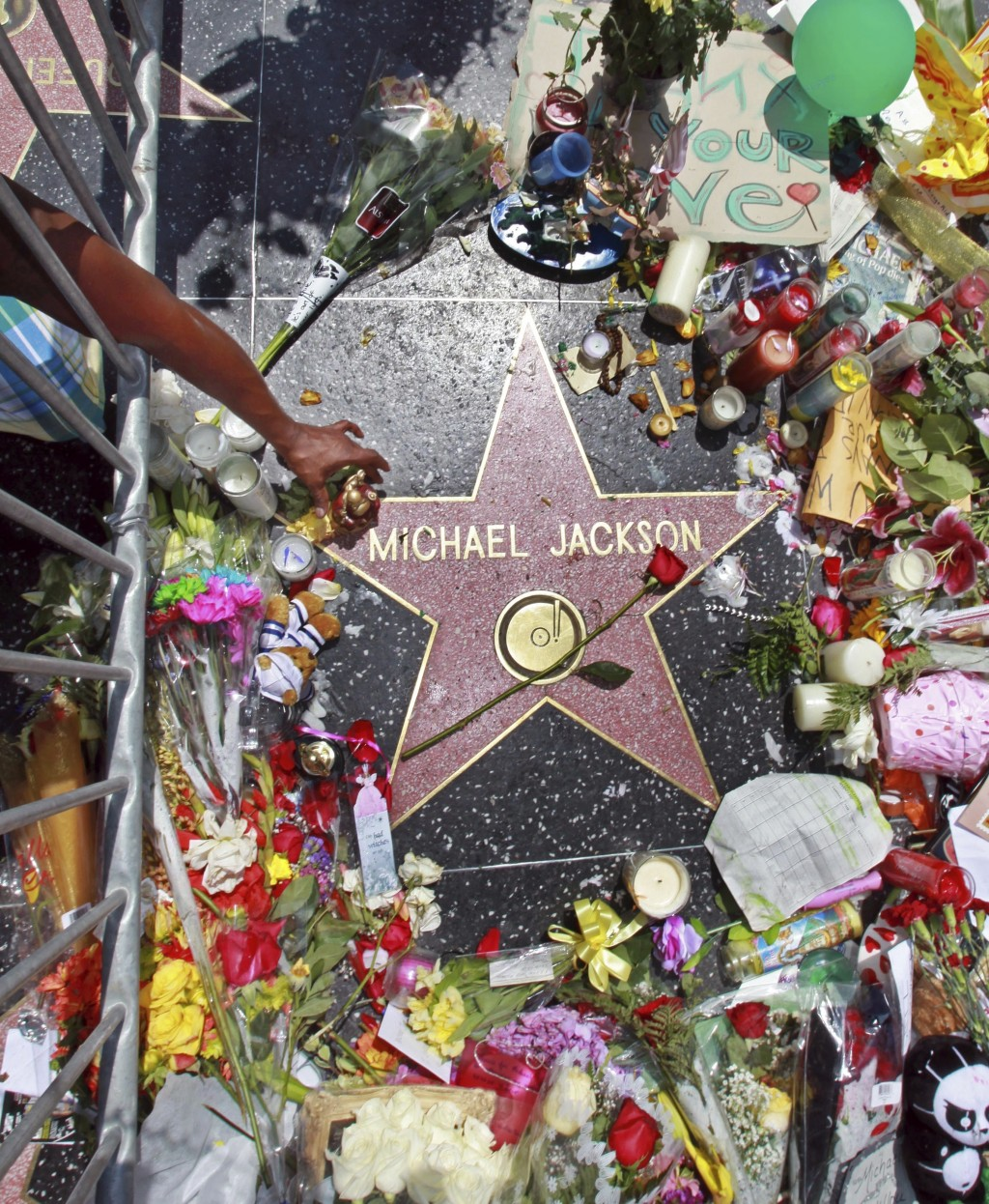 FILE - This June 26, 2009 file photo shows a sidewalk shrine of mementos, flowers and candles adorning the star of Michael Jackson on the Hollywood Wa...