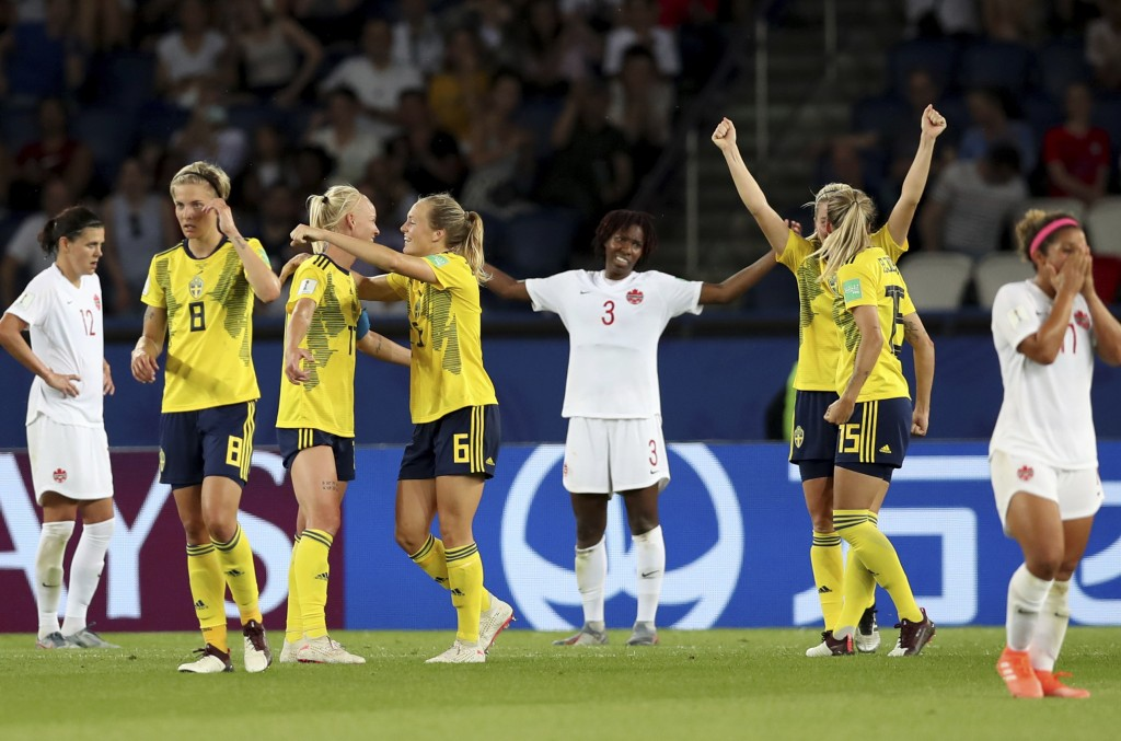 Team Sweden, left, celebrates after winning their Women's World Cup round of 16 soccer match between Canada and Sweden at Parc des Princes in Paris, F...