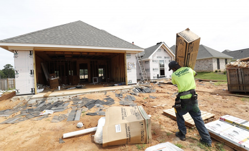 In this June 19, 2019, photo a worker carries supplies for a new house in a Brandon, Miss., neighborhood. On Tuesday, June 25, The Commerce Department...