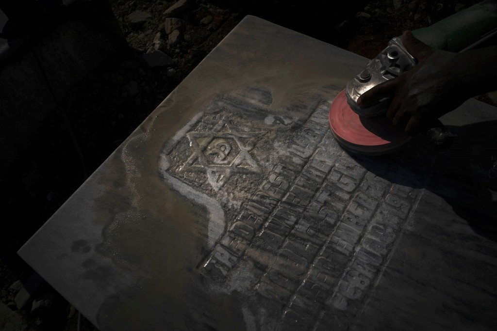 A worker polishes a tomb decorated with The Star of David at the Jewish cemetery in Guanabacoa, eastern Havana, Cuba, June 7, 2019. The restoration ef...