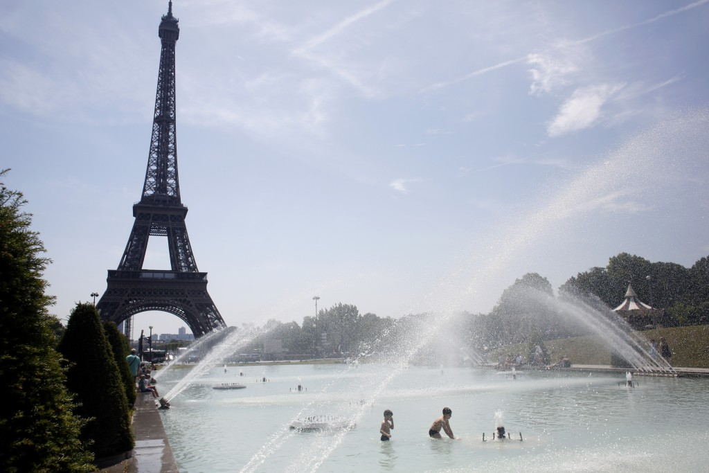 Children cool off in the fountain of the Trocadero, in Paris, Tuesday, June 25, 2019. More than half of France, including around Paris, was placed on ...