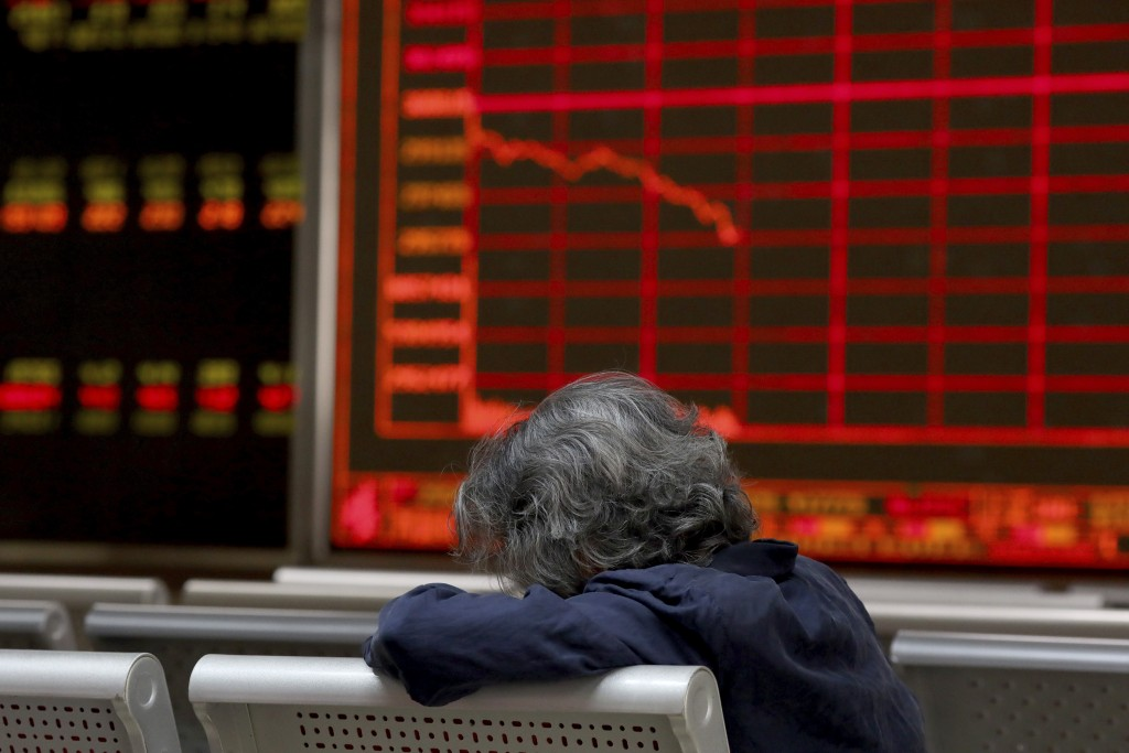 A woman rests as she monitors stock prices at a brokerage in Beijing on Tuesday, June 25, 2019. Major Asian stock markets declined Tuesday as traders ...