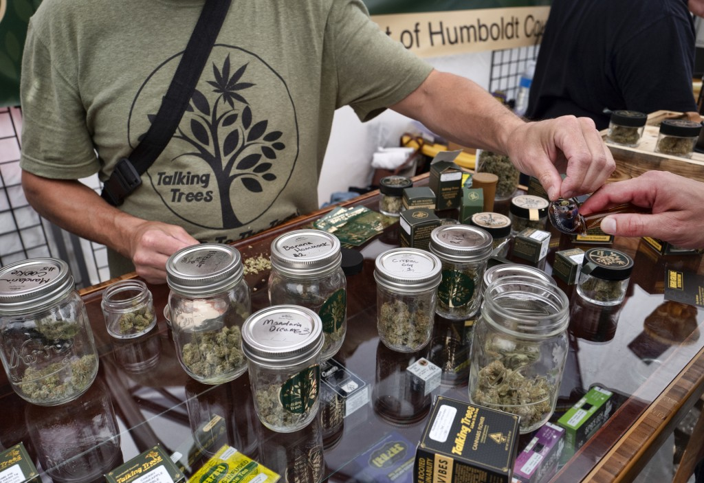 FILE - In this June 20, 2019 photo a vendor with Talking Trees Farms a Northern Humboldt County sustainable cannabis farm, offers a taste of their lat...