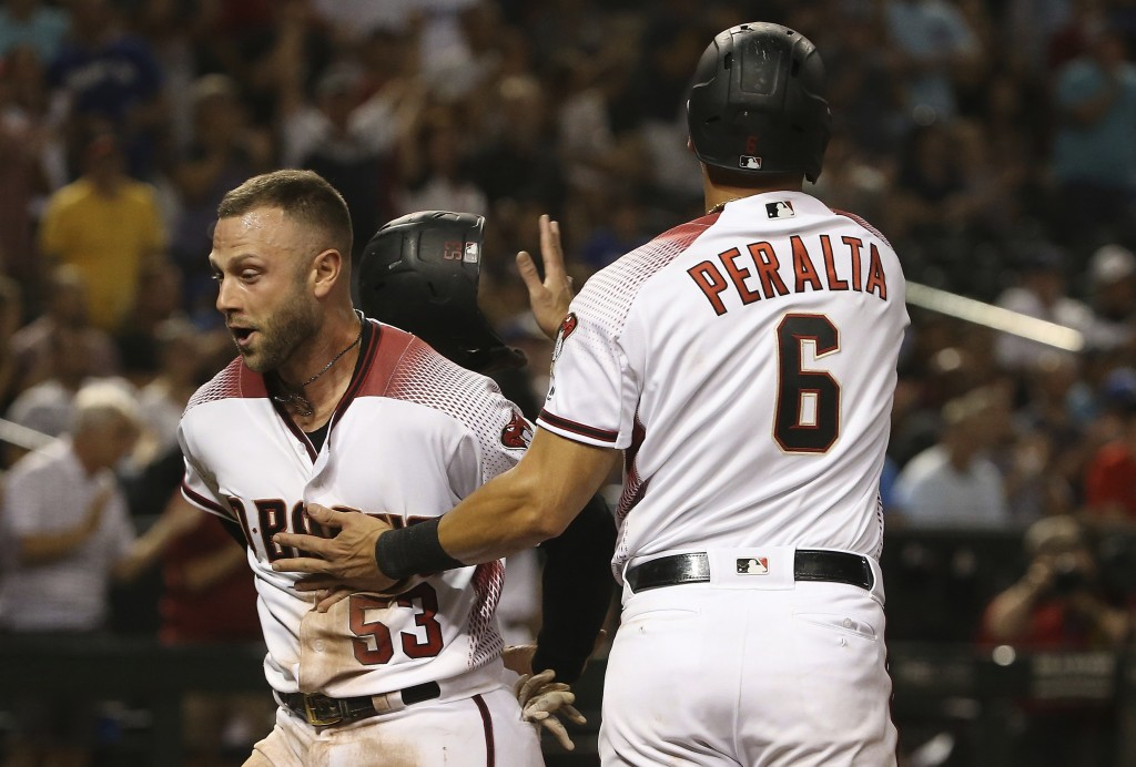 Arizona Diamondbacks' Christian Walker (53) and David Peralta (6) celebrate their runs scored against the Los Angeles Dodgers during the eighth inning...