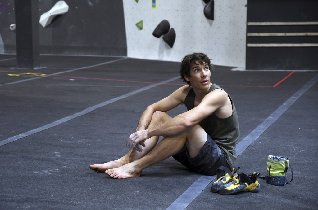 In this June 18, 2019, photo, professional rock climber Alex Honnold sits on the padded floor at the Earth Treks gym in Englewood, Colo. Honnold is tr...