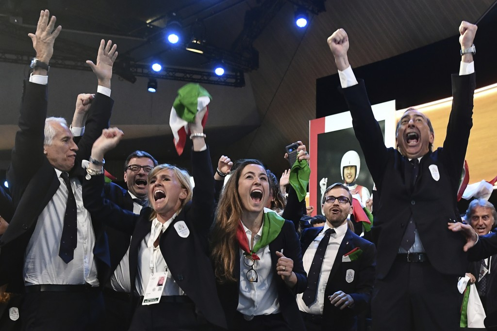Members of Milan-Cortina delegation celebrate after winning the bid to host the 2026 Winter Olympic Games, during the first day of the 134th Session o...