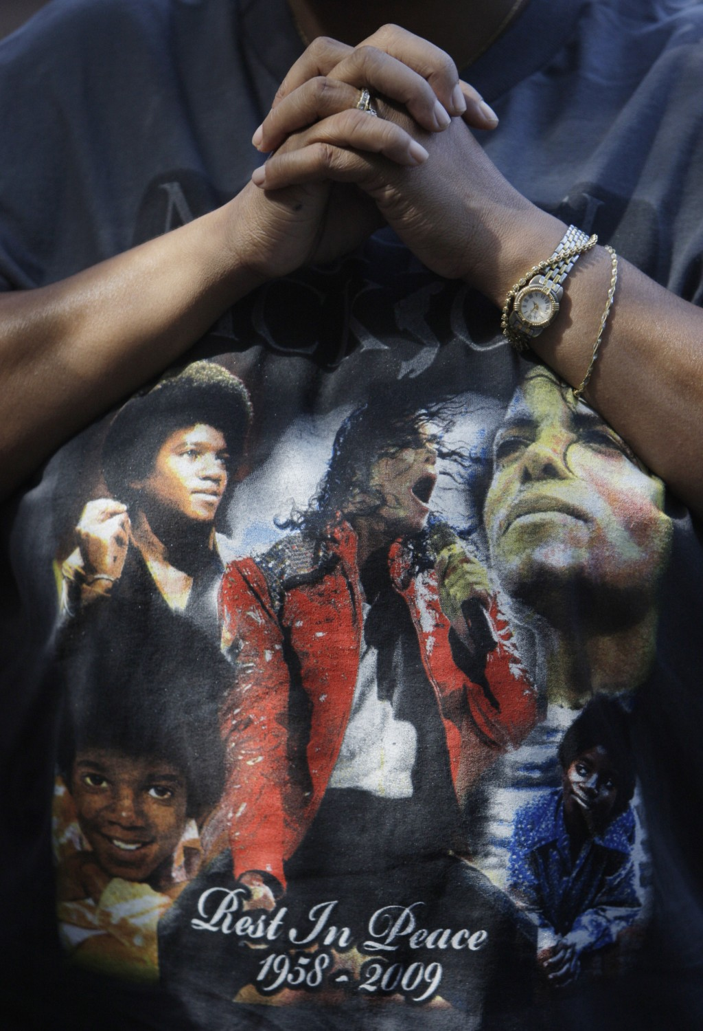 FILE - This June 30, 2009 file photo shows a fan wearing a Michael Jackson T-shirt at a makeshift memorial for the late pop star outside the Jackson f...