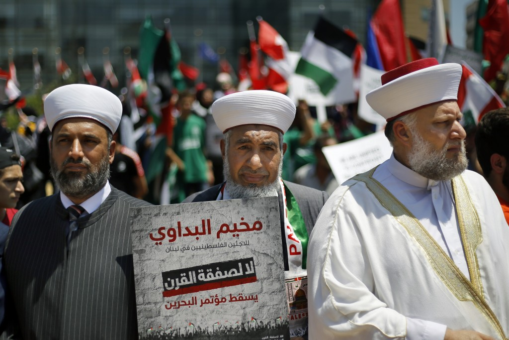 """A Palestinians cleric holds a placard with Arabic that reads: """"No to the deal of the century. Down with the Bahrain conference"""" during a demonstration..."""