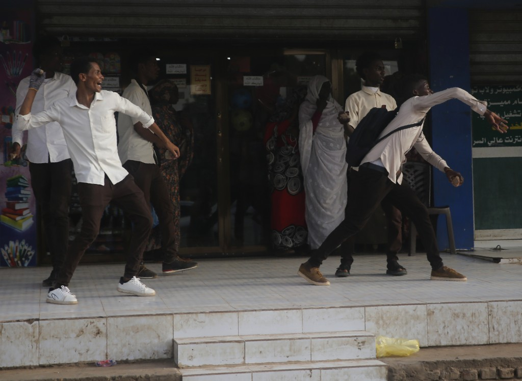 Protesters throw stones toward the riot police during a protest, in Khartoum, Sudan, Monday, June 24, 2019. A top Sudanese general is criticizing an E...
