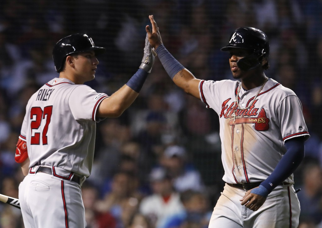 Atlanta Braves' Ronald Acuna Jr., right, celebrates with Austin Riley after scoring a run against the Chicago Cubs during the sixth inning of a baseba...