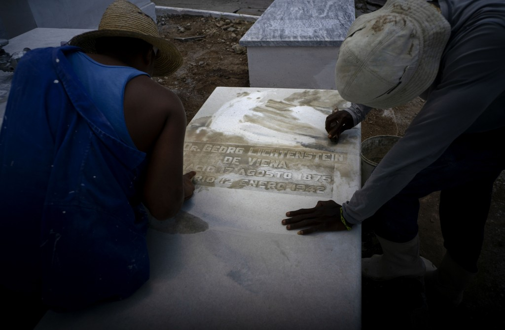 Workers clean the top of a tomb at the Jewish cemetery in Guanabacoa, eastern Havana, Cuba, June 12, 2019. Across the city, streets are being paved, m...