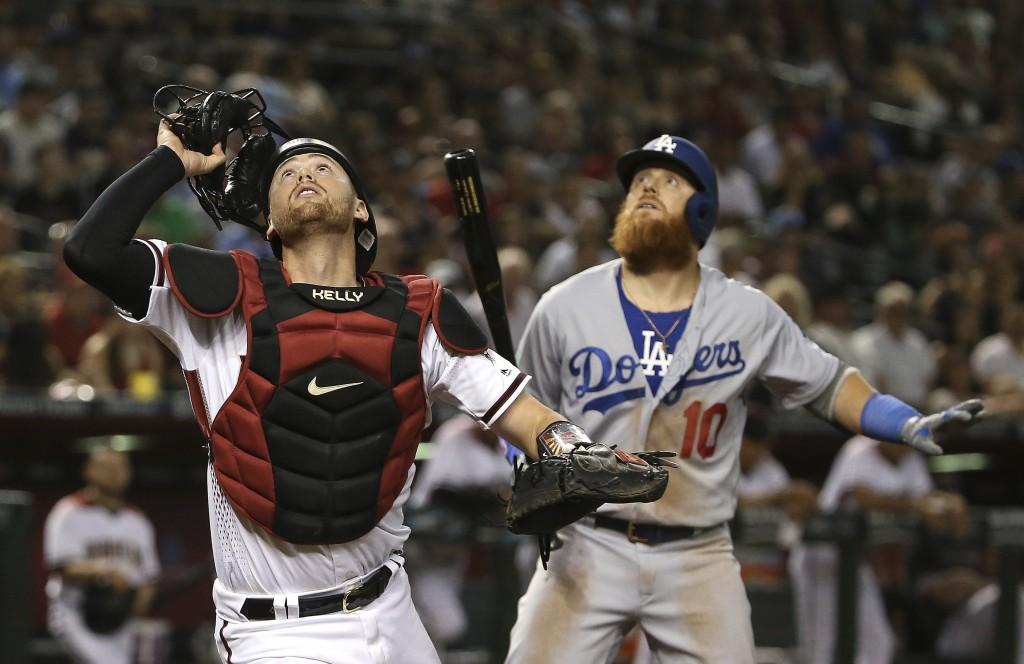 Arizona Diamondbacks catcher Carson Kelly, left, and Los Angeles Dodgers' Justin Turner (10) look up on a wild pitch by Diamondbacks relief pitcher Yo...