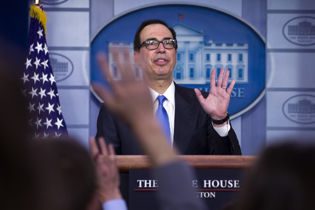 Treasury Secretary Steve Mnuchin waves as he departs after speaking to reporters about the new Iran sanctions in the Briefing Room of the White House,...