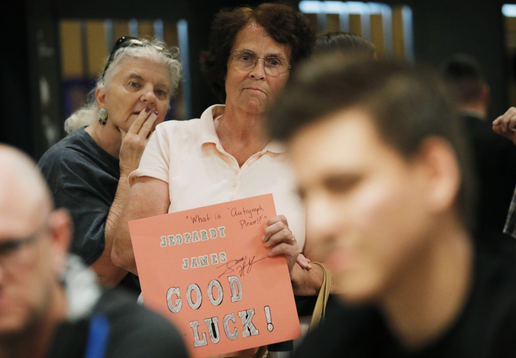 """""""Jeopardy!"""" fans Judi Blomquist, holding sign, and Susan Youngblood watch as """"Jeopardy!"""" champion and professional sports gambler James Holzhauer, rig..."""