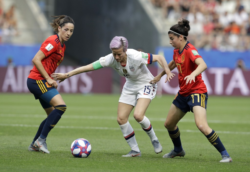 United States'Megan Rapinoe, middle, is challenged by Spain's Vicky Losada, left, and her teammate Lucia Garcia during the Women's World Cup round of ...
