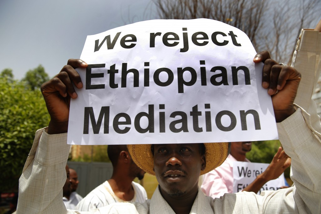 A Sudanese supporter of the military council, holds a placard during a sit-in against Ethiopian mediation, outside the Ethiopian embassy, in Khartoum,...