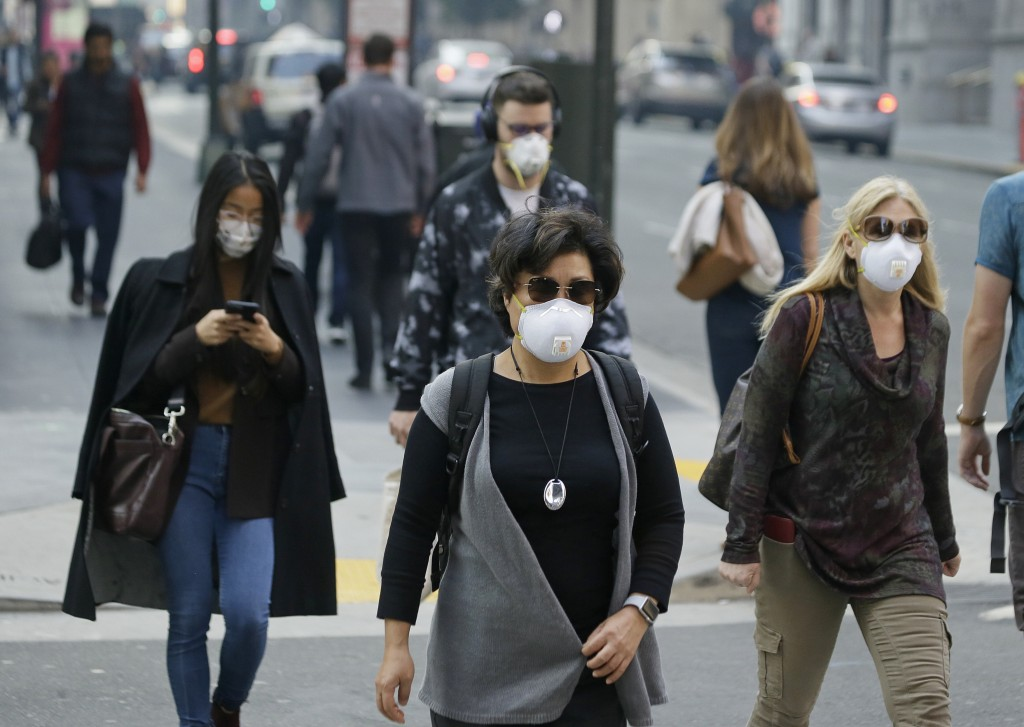 FILE - In this Nov. 9, 2018, file photo, people wear masks while walking through the Financial District in the smoke-filled air in San Francisco. Tens