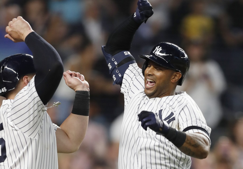 New York Yankees' Aaron Hicks, right, celebrates with designated hitter Luke Voit, after they scored on Hicks' three-run home run during the fifth inn...