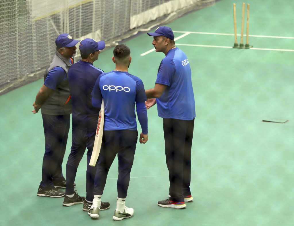 India's captain Virat Kohli, second right, listens to team coach Ravi Shastri, right, as he interacts with bowling coach Bharat Arun, left, and battin...
