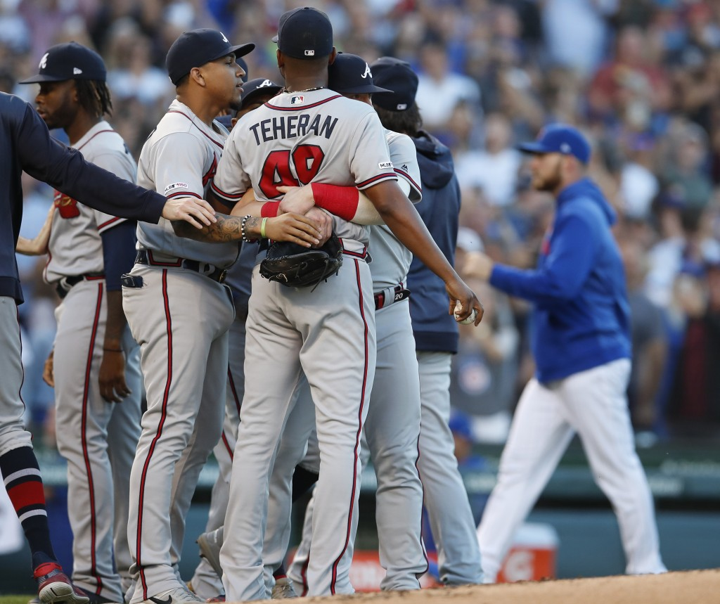 Atlanta Braves' Julio Teheran, center, is held back by Braves' Johan Camargo, second left, as the benches empty during a brief argument with the Chica...